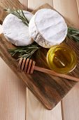 Camembert cheese and honey in glass bowl on cutting board on wooden background