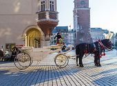 Horse Carriages In Front Of Mariacki Church On Main Square Of Krakow