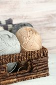Knitting yarn in basket, on wooden background