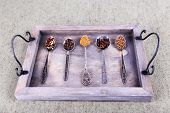 Seasonings in metal spoons on wooden tray on fabric background