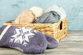Knitting yarn and mittens in basket, on wooden background