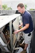 pic of hvac  - An HVAC heating ventilating air conditioning technician working on a large commercial unit - JPG