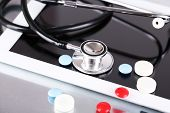 Stethoscope, pills, PC tablet on light background. medicine concept