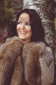 pic of muffs  - Portrait of a young smile woman wearing coat  and muff or handwarmer with a blurred nature background - JPG
