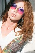 Attractive woman with an arm tattoo and long wavy brown hair wearing trendy sunglasses looking at the camera