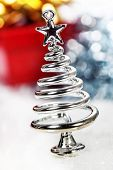 Silver stylized Christmas tree with decorations over white