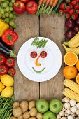 Smiling Face From Vegetables And Fruits On Plate With Tomatoes And Apples
