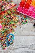 stock photo of loom  - Colorful elastic loom bands with band loom bracelets tools and hobby box - JPG