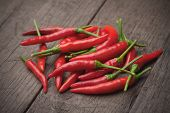 picture of chili peppers  - Red hot chili peppers on old wooden table - JPG