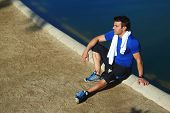 Attractive runner man sitting near artificial lake in park