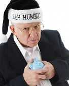 Close-up image of a grumpy old man clutching his piggy bank and wearing a black Santa hat saying