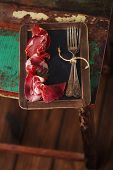 Cured Meat and vintage forks on textured Chalkboard and old wooden stool background