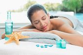 Beautiful young woman lying on massage table at spa center