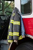 Firefighter suit Hanging on the Door of Fire Truck Closeup