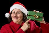 Smiling Mature Woman Pointing At Wrapped Xmas Gift.