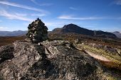 A stone cairn on a hiking route with a view of the Bitihorn Mountain, Oppland region, Norway