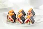 Maki Sushi - Sushi Roll with Cucumber, Tamago, Salmon Roe, Tobiko and Cream Cheese inside. Nori outside. Topped with Salmon