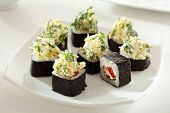 Sushi Roll made of Tomato, Cheese and Lettuce inside. Nori outside. Topped with Cheese and Lettuce