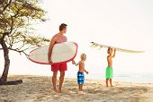 Father and Two Young Sons Going Surfing at the Beach