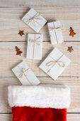High angle image of a Christmas Stocking with five plain white paper wrapped gifts tied with string on a whitewashed wood table. Vertical Format.