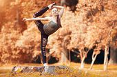 Beautiful woman exerciser in autumn park