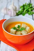 Vegetarian pumpkin soup in orange bowl on a wooden table