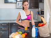 Pretty attractive athletic sportive lady woman standing in kitchen with a towel on her shoulder and