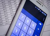 A Smartphone Calculator Next To Financial Documents