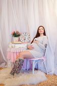 Beautiful pregnant woman sitting on a chair and hugs her belly