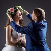 Lesbian wedding. Groom puts wreath on bride's head