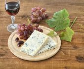 Cheese, grapes and wine on wood