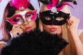 picture of venetian carnival  - Two women mixed race and caucasian with carnival venetian masks and black feather fan - JPG