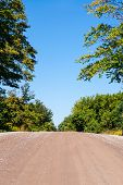 Empty Dirt Road Rising Against Trees And Sky