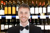stock photo of bartender  - Portrait Of Smiling Male Bartender In Front Of Wine Shelves - JPG