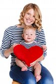 Happy mother and her little son holding a pillow in the form of red hearts.