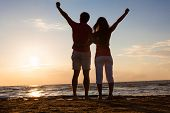 Couple With Hands Raised At Beach During Sunset