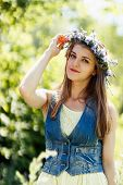 pretty young woman touching flower wreath on her head