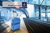 Departure For Kuala Lumpur, Malaysia. Blue Suitcase At The Railway Station