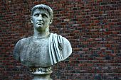 Ancient weathered Roman bust of man against red brick background