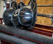 foto of firemen  - Row of antique black firemen helmets hanging up - JPG