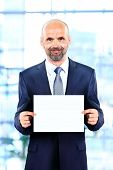 Happy senior businessman holding Blank business card in the office