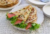 Thin rolled pancakes, crepes with salmon, . Traditional Russian dish.