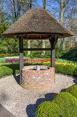 stock photo of groundwater  - New water well with bucket in green park with blue sky - JPG