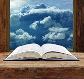 Bible open book wooden window sky view stormy cloud