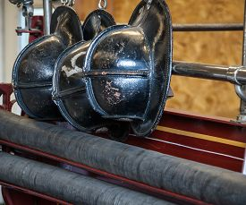 picture of firemen  - Row of antique black firemen helmets hanging up - JPG