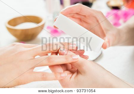 poster of Closeup shot of a woman in a nail salon receiving a manicure by a beautician at nail salon. Woman us