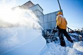 pic of snow shovel  - Worker in yellow winter jacket removes snow near his garage with a snow throwing machine at a sunny winter day - JPG