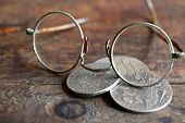 stock photo of spectacles  - Three ancient Russian silver coins near spectacles on wooden background - JPG