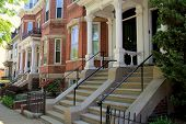 stock photo of stone house  - Beautiful craftsmanship in quiet city street lined with brick and stone row houses - JPG