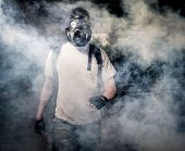foto of gas mask  - Man in a gas mask walking through the smoke - JPG